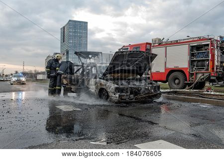 RIGA LATVIA - APRIL 11 2014: Out into the road stands just doused car. Firefighters inspected losses. Traffic is stopped.