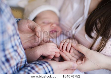 Mother and father holding hand of sleeping baby. Parents with Newborn Baby Boy.