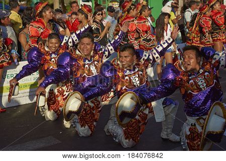 ARICA, CHILE - FEBRUARY 10, 2017: Male members of a Caporales dance group in ornate costumes performing at the annual Carnaval Andino con la Fuerza del Sol in Arica, Chile.