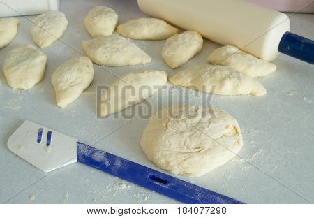 dough, rolling pin, flour for making fresh homemade cakes.
