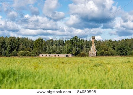 Rural landscape with dilapidated old houses and chimney.