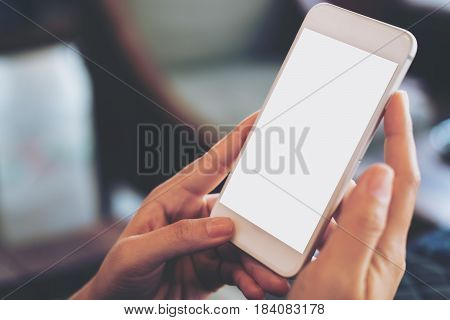 Mockup image of hand holding mobile phone with blank white screen in vintage cafe