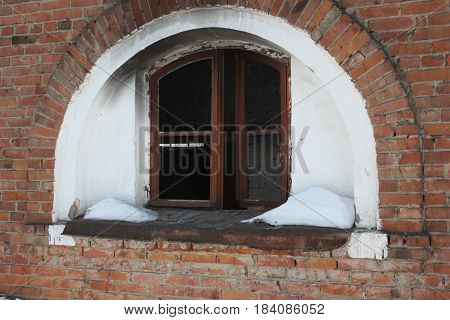 Broken window half arch on red brick wall. Eerie building. . Abandoned building. Photo for your design.