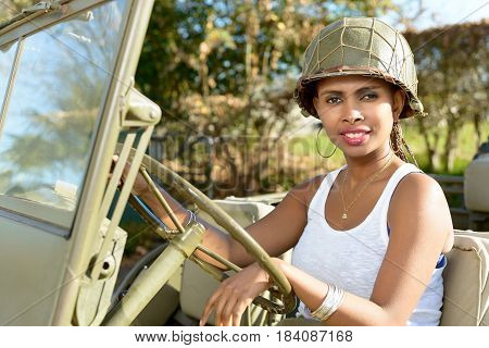 beautiful smiling young woman with a ww2 military helmet