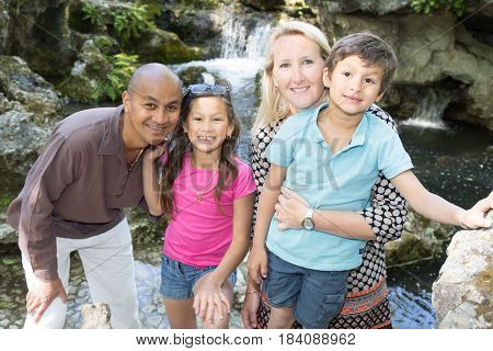 Holiday Souvenir Picture Of A Mixed Family In Front Of A Waterfall