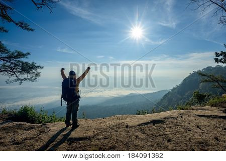 Man on the top of a rock to face the sunrise - success concept