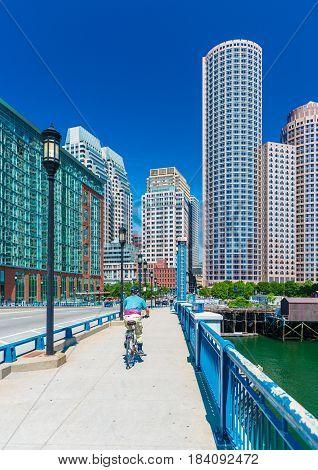 Boston, MA - June 2016, USA: Man cycling on bridge towards Boston downtown in sunny summer day