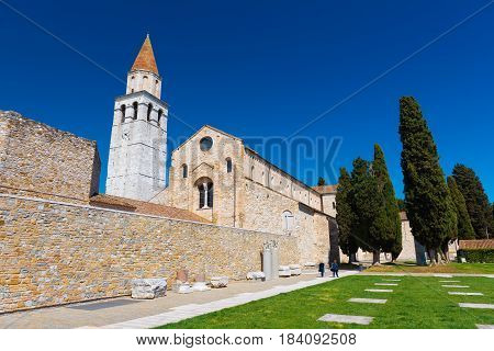 Aquileia - April 2016, Italy: Ancient Roman city of Aquileia, wide angle view of the main landmark - Basilica di Santa Maria Assunta and old ruins nearby