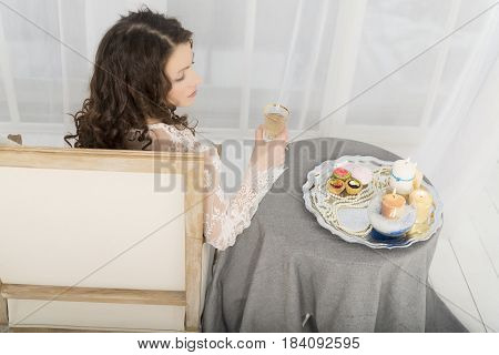 Girl In A White Dress Sitting At A Table