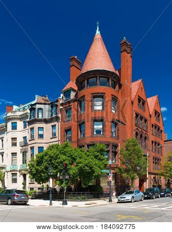 Boston, MA - July 2016, USA: Old historical building made of red brick and brownstone with cone rooftop in Boston back Bay district against the backdrop of a clear blue sky