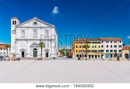 Palmanova - April 2016, Italy: Central square in The Fortress - Town of Palmanova, view on Cathedral and colored houses in traditional architecture style