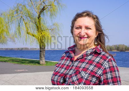 A portrait of a happy smiling woman on a background of river and willows