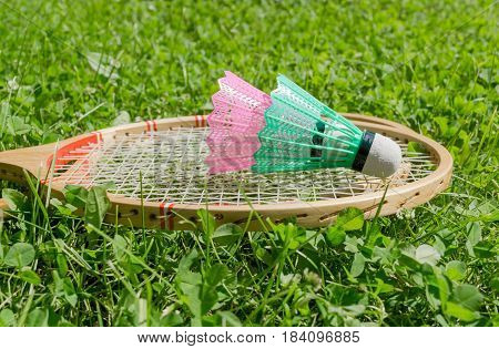 Badminton Rackets And Shuttlecocks On Grass