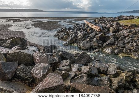 A creek flows past boulders into the Puget Sound at Saltwater State Park in Des Moines Washington.