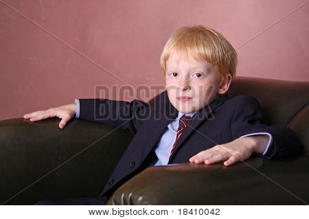 young boy dressed up sitting on a chair
