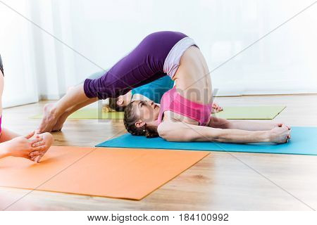 Portrait of group of people practicing yoga at home. Halasana pose.