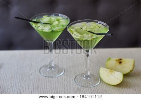Two glasses of apple martini and apple slices on table in cafe