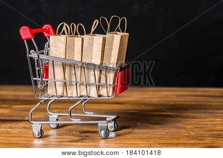 concept of friday sale with shopping trolley paper bags on wooden background over black close up