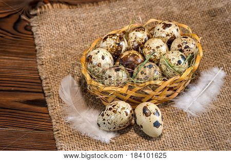 Quail Eggs With Straw And Feathers In Basket On Hessian Wooden Background, Rustic Style, Close Up
