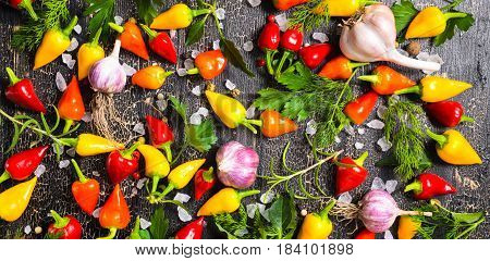 Top View Of Ripe Yellow, Red Hot Chili Peppers, Sea Salt, Different Greenery, Black Peppers And Garl