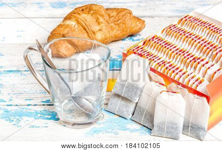 Empty tea cup with tea bags and croissant on the table.