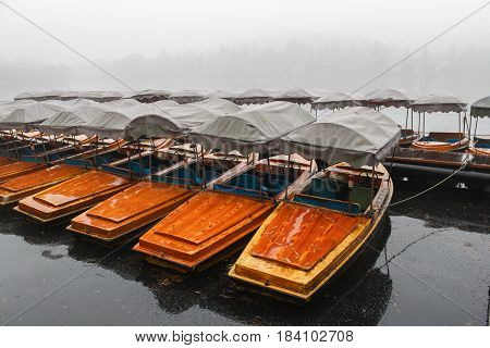 Many boats waiting for tourists on a misty lake