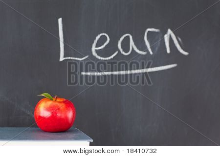"""Stack Of Books With A Red Apple And A Blackboard With """"learn"""" Written On It"""