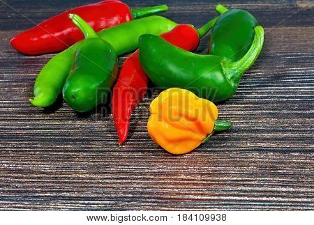Bunch of fresh chilli chilli peppers piled up together. The vegetable belongs botanically to the Genus Capsicum, being members of the nightshade family, Solanaceae. Closeup image.