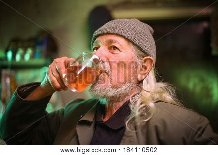 An old man drinking from a glass of wine.