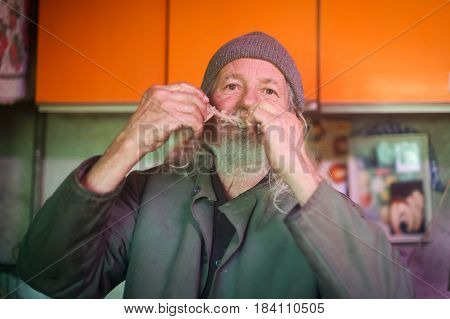 A front view of an old man gnawing on a pork bone and looking at camera.