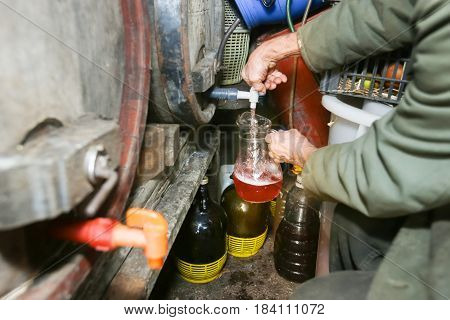 A man pouring homemade wine from a barrel into the pitcher.