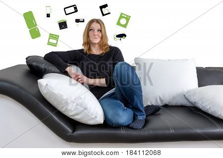 Closer view of grinning long haired young woman sitting on a black and white couch with black and white pillows. Woman is looking upwards on the illustration of a home appliance in the background.