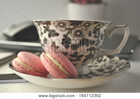 A black and white floral tea cup with pink French macaroons on a table with laptop computer and a mouse - a  work from home workstation