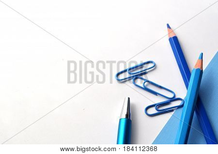 A flat lay image with lots of negative space for text , book, blue pencils with copy space