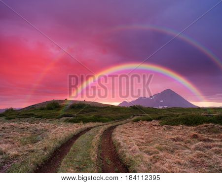 Midnight sun and an amazing rainbow in Iceland. Fantastic beautiful dawn. Dirt road on the mountain hills