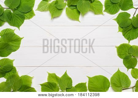 Decorative frame of green linden leaves on a white wooden background. Template for design. Flat layout, top view