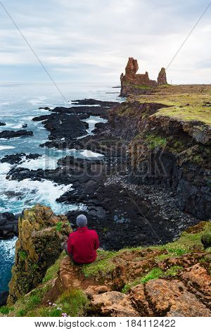 Tourist guy sits on a rock and looks at the ocean. Cliffs of Londrangar, a famous tourist attraction of Iceland