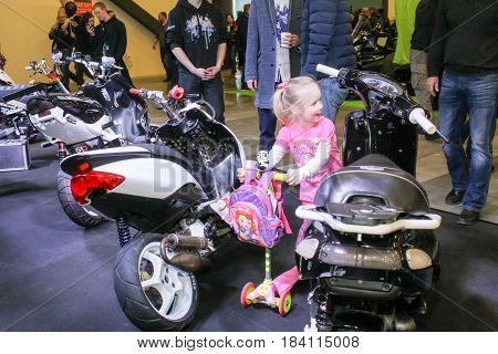 St. Petersburg Russia - 15 April, A little girl between scooters,15 April, 2017. International Motor Show IMIS-2017 in Expoforurum. Visitors and participants of the annual moto-salon in St. Petersburg.