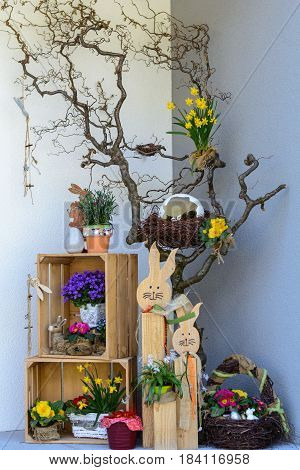 Creative upcycling Easter decoration before home entrance with flowers and Easter bunny