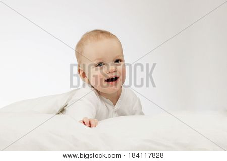 Cute smilling 9 month boy in white bodysuite on white background. Laughing infant kid under blanket. Copy space