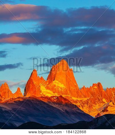 Blood-red sunset illuminates the top of impressive cliffs Fitz Roy. The stunning Patagonia