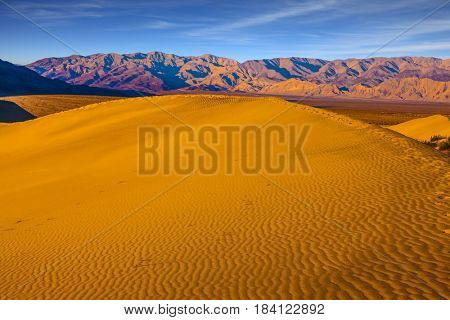 Early morning  in a picturesque part of Death Valley, USA. Small ripples of sand orange. Mesquite Flat Sand Dunes