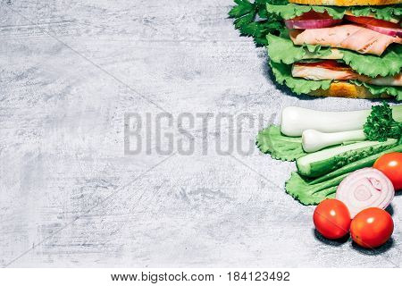 Double sandwich of bread, ham, cheese, tomato, cucumber, onion and lettuce and its ingredients on spotty blue background.