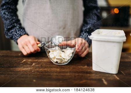 Female hands holds spoon with margarine over bowl