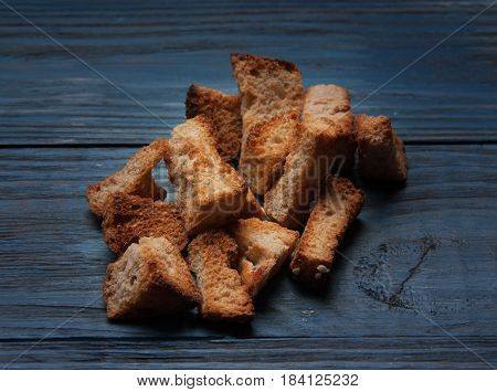 Heap of small rusks from black bread on a rustic wooden table