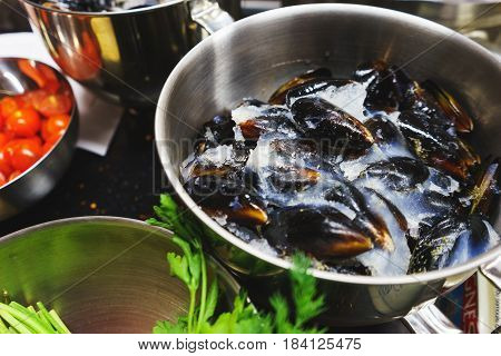 Chilled mussels cooked for cooking in the kitchen in a metal saucepan. The process of making pasta with seafood. Top view of a mussel with ice in a metal vessel. Soft selective focus.