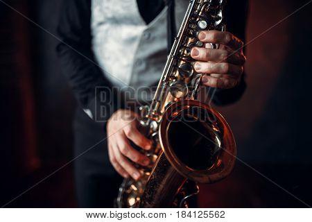 Jazz man hands holding saxophone closeup
