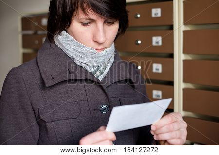 A girl in a coat carefully looking on the account received by mail.