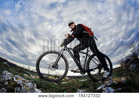 Photo below of the mountain cyclist in the black sportwear on the rocks against dramatic sky with clouds. Cyclist in the helmet, sunglasses and with red backpack. Beautiful landscape. Summer season in the coutryside. Healthy lifestyle.