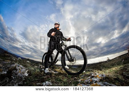 Photo below of the mountain cyclist in the black sportwear on the rocks against dramatic sky with clouds. Cyclist in the helmet and sunglasses. Beautiful landscape. Summer season in the coutryside. Healthy lifestyle.